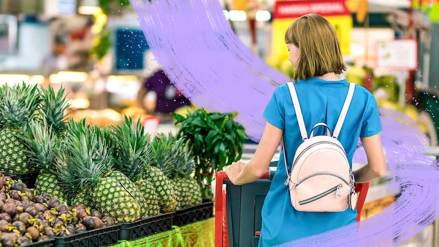 A woman pushes a shopping trolley past a display of fresh pineapples, adding to her incidental exercise.