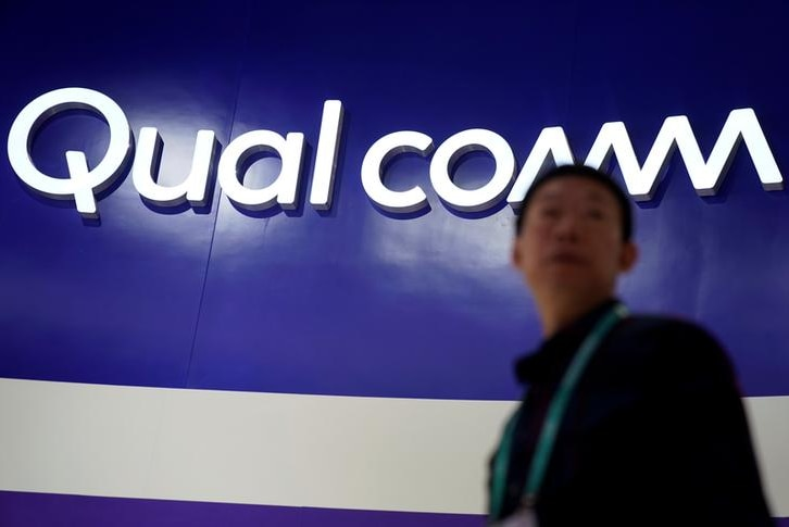 Qualcomm sign on blue background with Chinese man standing in front