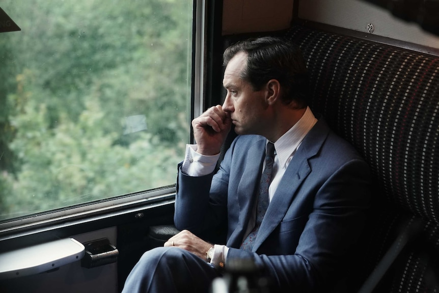 Jude Law in a suit on a train staring out the window stressed in the film The Nest