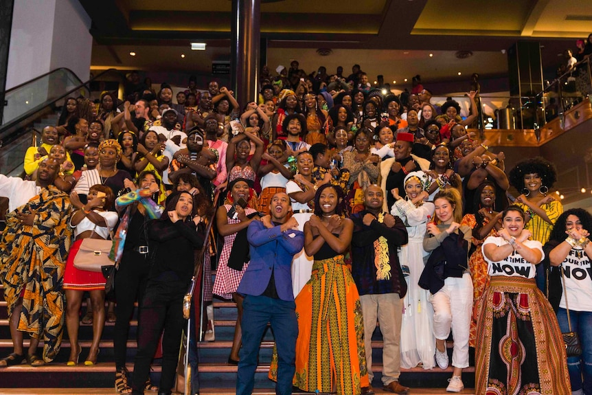 A crowd of mostly African people pose at a movie cinema.