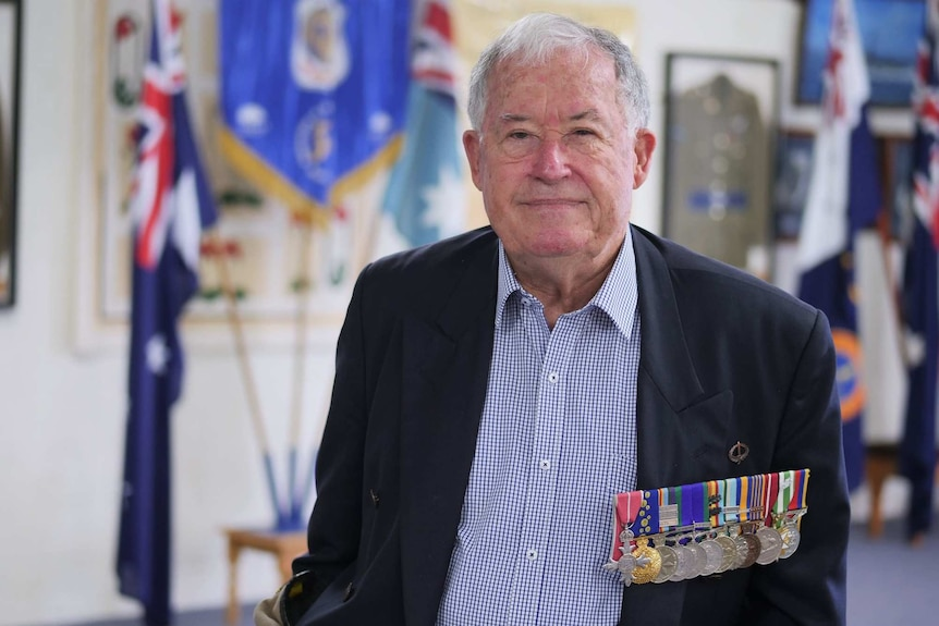 Laurie Fisher, wearing his medals, in front of a military display at the Albany RSL Club.