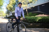 Giles wears work attire while riding a bike.