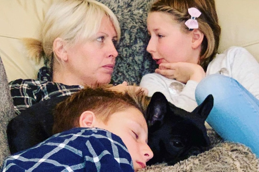 A woman and two kids relax on a bed with a black dog