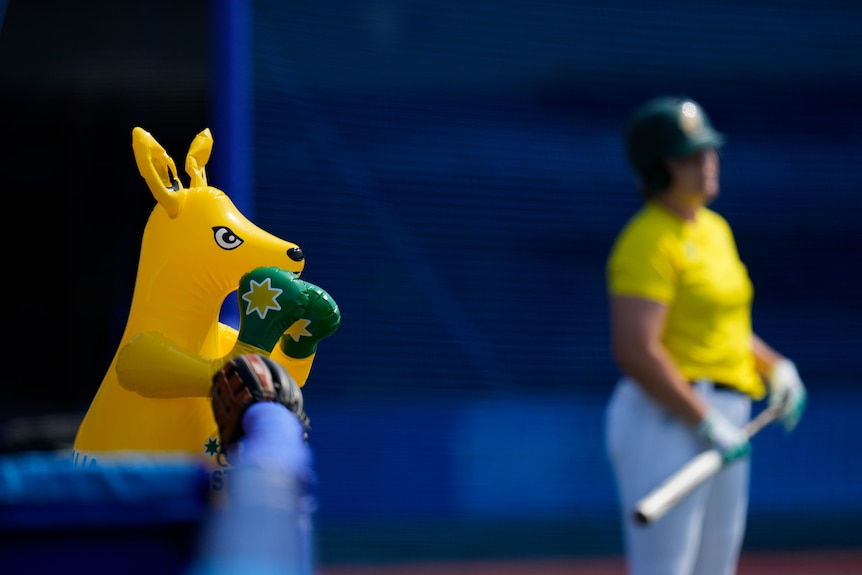 A yellow inflatable boxing kangaroo rests on a fence with a softball player in the background.