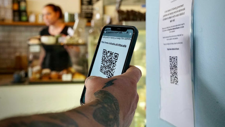 a tattooed hand holding a phone over a QR code in a cafe
