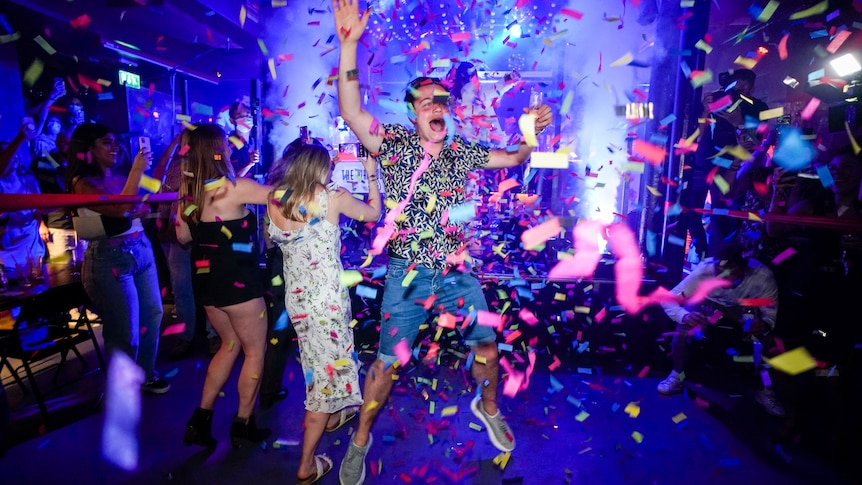 A man wearing a colourful shirt and shorts jumps in the air as pink streamers fall from the ceiling of a club.