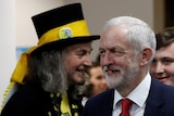Labour leader Jeremy Corbyn at a counting centre in London, walks past a member of the raving loony party