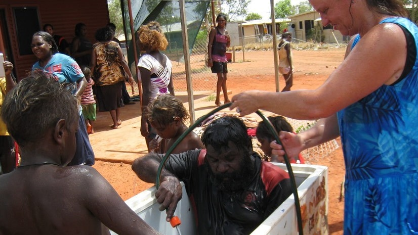 An Aboriginal man sits in a bathtub, with a white woman standing above him handing him a hose. He is holding the end of the hose