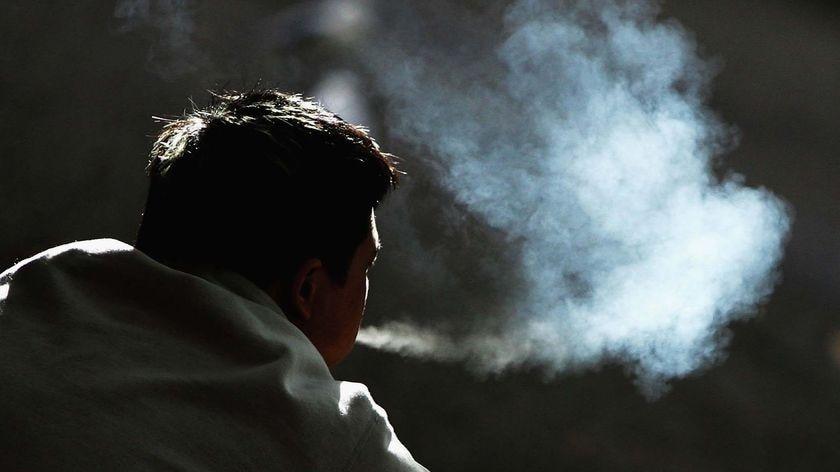 Silhouette of man smoking a cigarette
