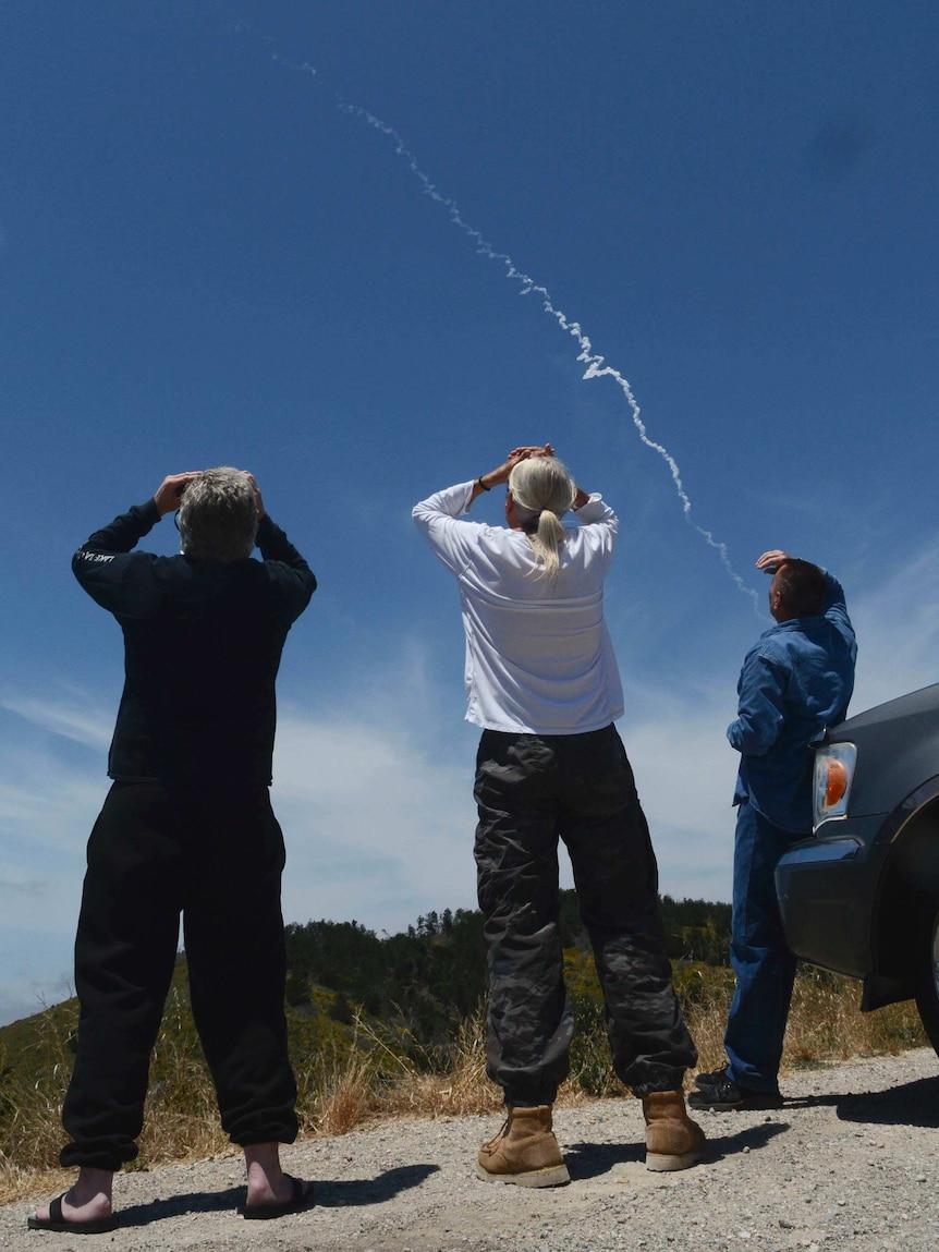 Three spectators watch aninterceptormissile traverse a blue sky.
