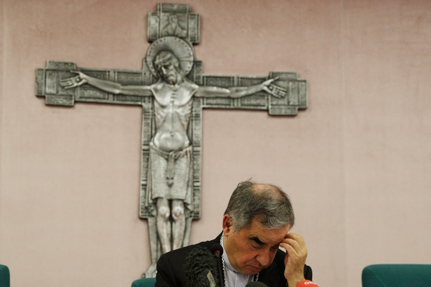 A middle aged man in a suit jacket puts his left fingers on his forehead as he looks down, sitting before a crucified Jesus.