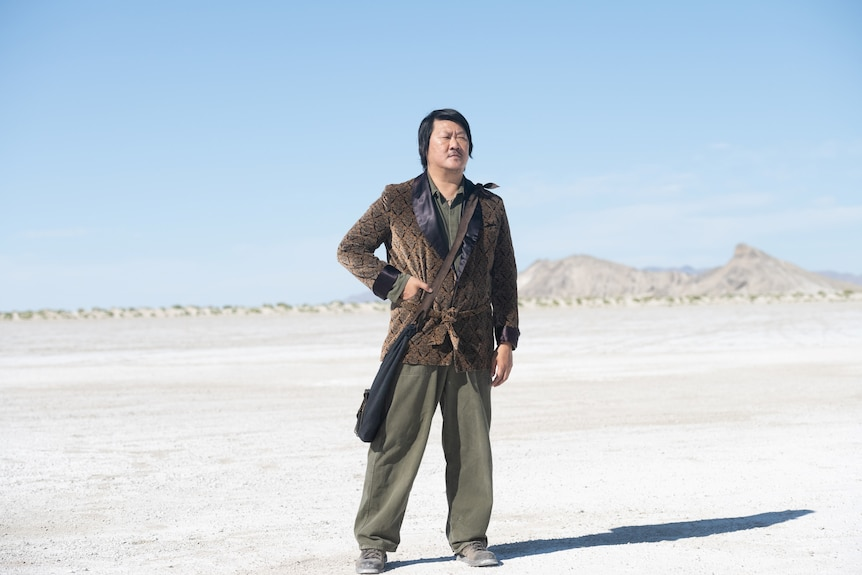 A 50 year old Chinese man in a suit jacket and green slacks with a bag slung across his shoulder stands in a desert