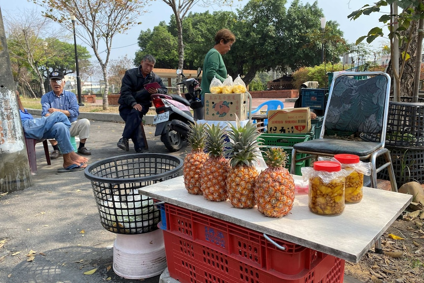 Some fresh and bottled pineapples sit on a table with old people sitting around.