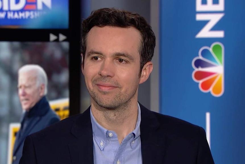 John Hendrickson smiles as he sits on an NBC News set.
