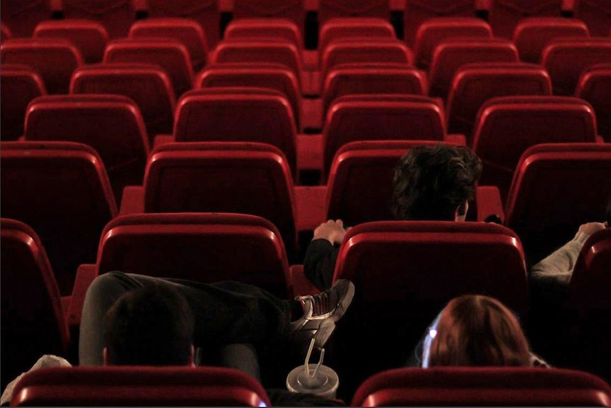 People watch a movie in a mostly empty cinema