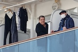 Two male passengers leaning on their railings on board the Diamond Princess