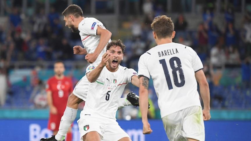 Three Italian players jump and celebrate