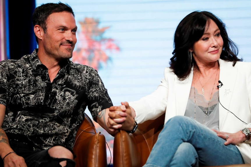 A man in a black patterned shirt and a woman in a white jacket sit in chairs holding hands.