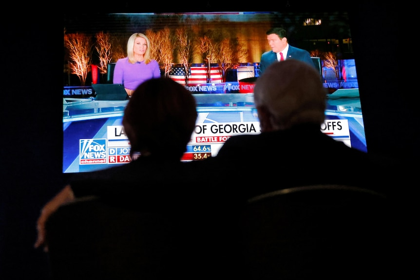 Guests watch news coverage of the run-off election for Georgia's two Senate seats.