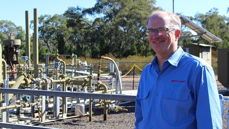 Santos vice president Bruce Clement standing in front of a gas well in the Pilliga forest in NSW.