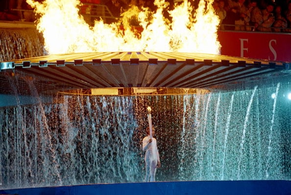 A woman stands with a flaming torch, as a large ring of fire rises behind her with water cascading off it