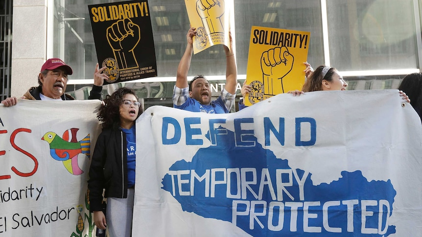 Protesters hold up signs calling for immigrants to keep temporary protected status.
