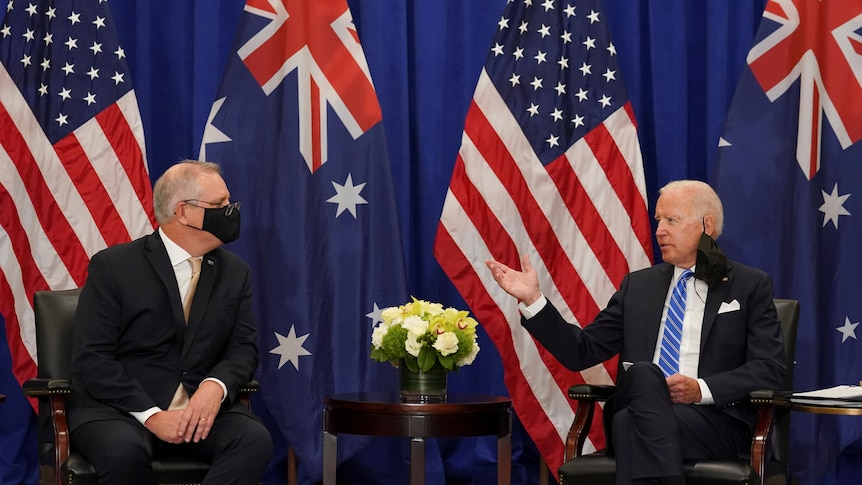 Two suited men sit and talk in front of two Australian and two US flags.