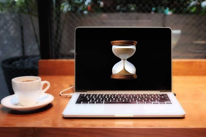A laptop computer displaying an hourglass emoji sits next to a cup of coffee on a desk.