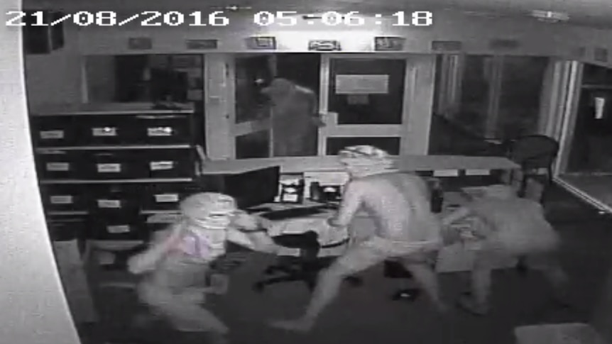 CCTV still of the four hooded , shirtless young makes in the office