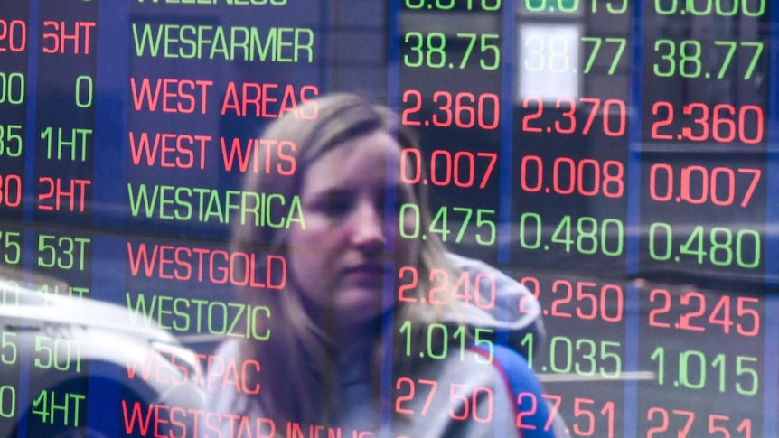 A woman is seen in the reflection of a window looking at shares' performance on a board of the ASX