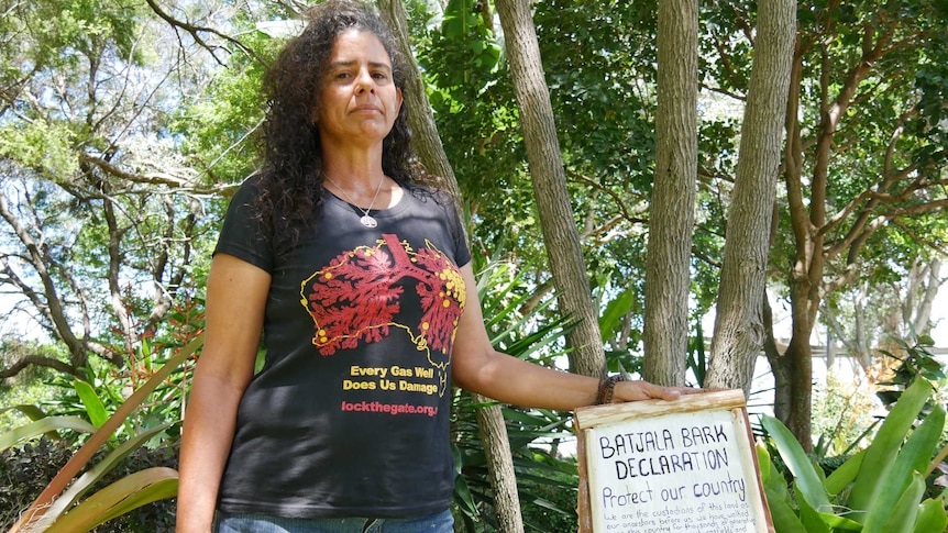 A woman stands with a declaration, written on bark, calling for the government to ban fracking.