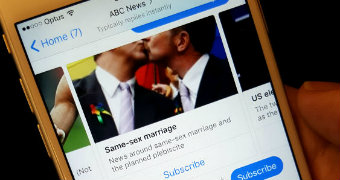 A close-up photo of a person holding a phone displaying a message from ABC News on Facebook Messenger.