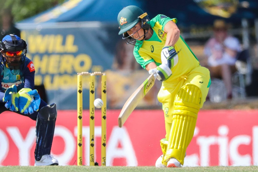 A female Australian cricketer hits to the off side as the Sri Lanka wicketkeeper looks on during the ODI.