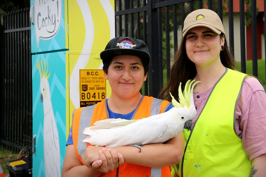 Artists Tanya Rivera and Kiana Kilford, with Tanya holding her pet cockatoo on her arm.
