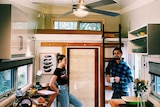 A young couple inside a tiny house that looks about the size of a large caravan. A ladder leads to a loft bed.