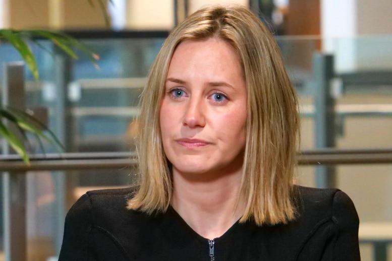 A blond woman wearing a dark jacket listening during an interview.