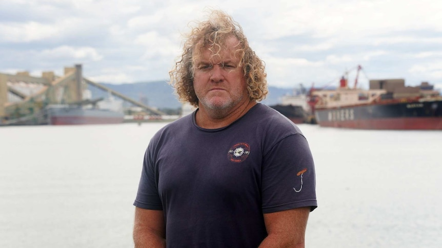 A well-built man with long, curly hair standing in front of a harbour.