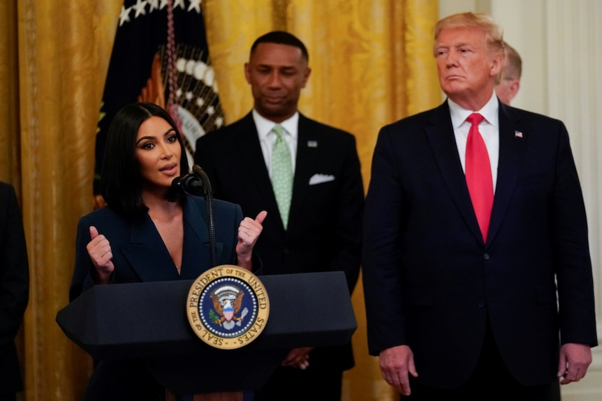 Kim Kardashian West speaks behind a lectern with a US presidential seal as President Donald Trump watches on.