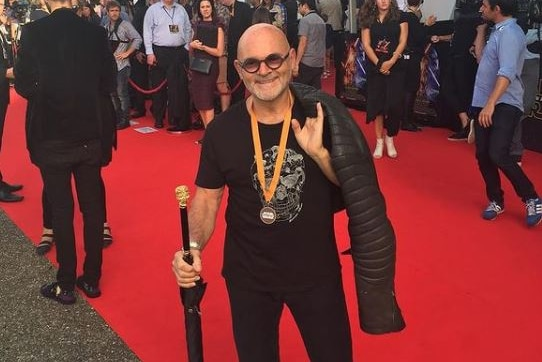 A man wearing glasses walks on a red carpet