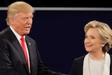Donald Trump and Hillary Clinton smile as they shake hands during the second US presidential debate.
