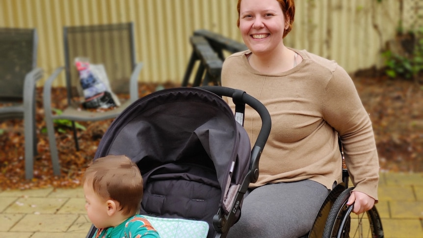 Molly is smiling and has both hands on her wheelchair's wheels. Her son is in a pram attached to the front of her chair.