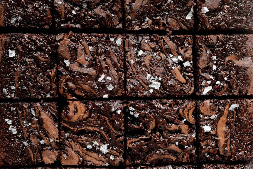 A batch of salted caramel brownies with sea salt sliced and ready to serve.