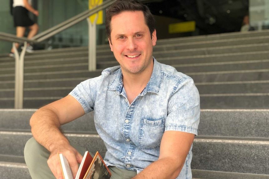 A young man sits on a step holding a book.