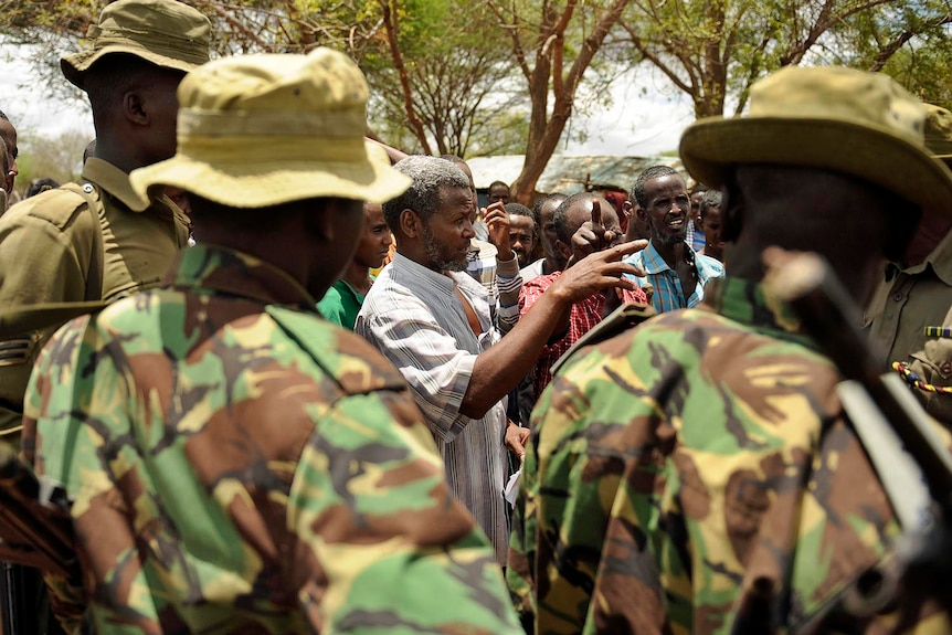 Kenyan security forces talk with residents at a village near Kenya's border town with Somalia on October 15, 2011.