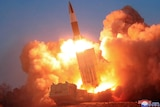 A missile launches into the air, leaving behind red plumes of smoke.