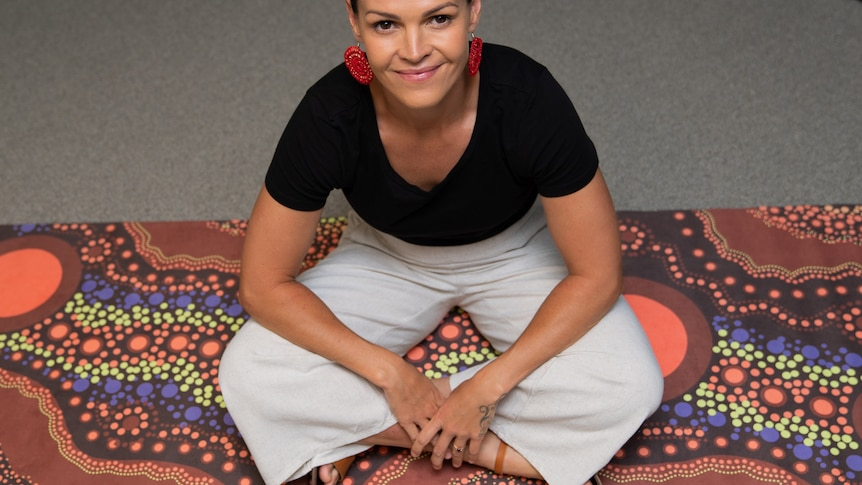 A young woman sits cross legged, smiling on top of a mat featuring an Aboriginal design.