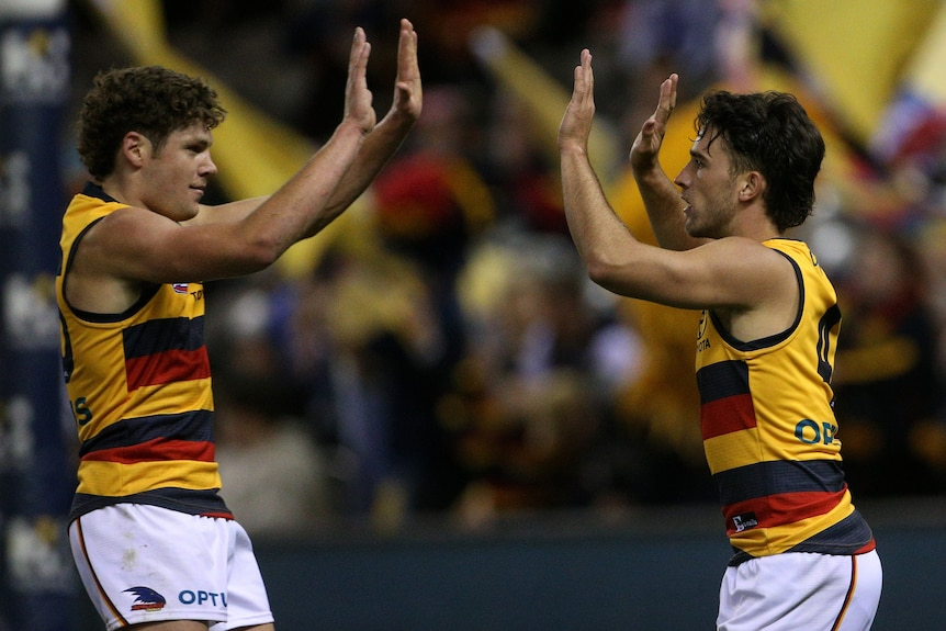 Two Adelaide Crows AFL players give each other a high five as they celebrate a goal.