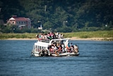 A boat full of Chinese tourists in the river in Dandong.