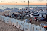 Tables and chairs with striped umbrella are set up on a beach at sunset
