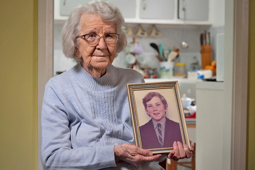 Image of an elderly woman holding a photograph of a young boy.